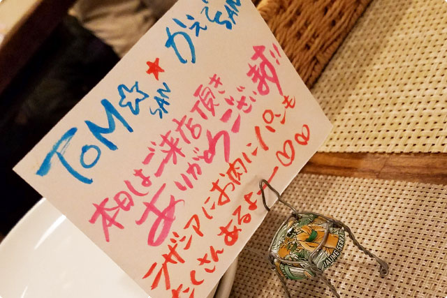 """It's saying """"Dear Tom and Kaede! Thank you for your visit xD Please enjoy your dinner xD"""""""